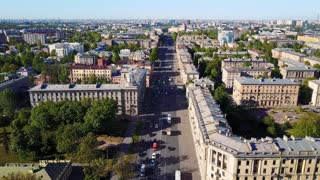Aerial view. Crossroads in the downtown of city, vehicles drive through the solar part of the road, aerial view. St. Petersburg, Russia