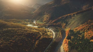 Aerial View Drone Flight over fantastic canyon mountain river. Dramatic autumn nature landscape. Green meadows, orange hills, pine tree forests against sunset sky. Carpathians, Ukraine, Europe. 4K