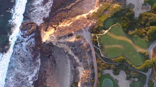 Aerial view from above of a coastal golf course fairways with luxury homes at sunset.