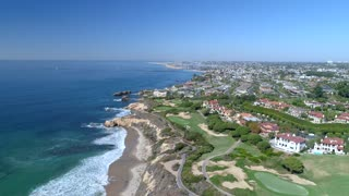 Aerial view of a coastal golf course fairways with luxury homes.