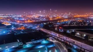 Aerial view of urban freeway and city skyline at night
