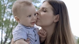 Affectionate mother talking and kissing fussy little boy while spending time outside on summer day