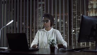 African businesswoman typing on computer and laptop sitting in office at night