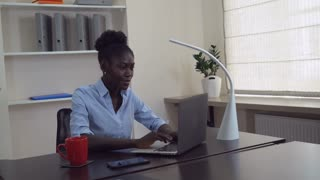 Afro american businesswoman working in office. Young professional woman sitting at the working place typing on computer. Happy manager chatting online or entering data on laptop