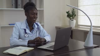 Afro american doctor chatting online with client. Professional woman wearing in white coat on her neck phonendoscope. Physician sitting at the desk use computer talking with patient