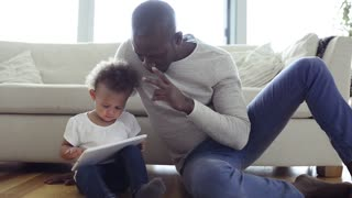 Afro-american father with little daughter at home holding tablet.