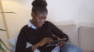 Afro american woman sitting on the couch using digital tablet for surfing internet or for chatting online or work with document at home. Girl wearing casual trendy sweater and jeans