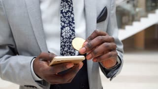 Afroamerican Businessman with bitcoin and mobile phone in Modern Office.