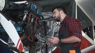 Aircraft mechanic carefully inspecting engine of plane using digital tablet