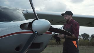 Aircraft mechanic polishing plane and then standing satisfied with his job