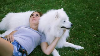 An adult woman with red hair lying on her dog of the Samoyed breed. White fluffy pet in a park with mistress on a green lawn have fun. SLOW MOTION