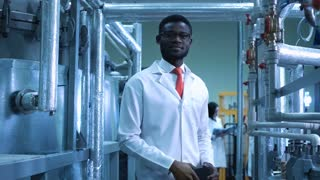 An African smiling scientist looking at camera standing in a plant. Horizontal indoors shot