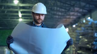An architect looking in the blueprint and smiling in the warehouse