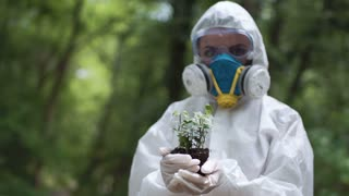 Anonymous person in protective suit holding pile of earth with small sprout in woods