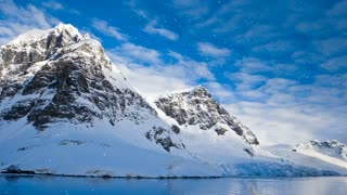 Antarctic Nature. Snow-capped mountains against blue cloudy sky with snow falling. Majestic winter landscape. Exploring beauty world, holidays and recreation. Travel background. Slow motion 4K