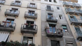 Apartment building streets in Barceloneta area. House with balconies in Barcelona's Gothic Quarter. Facades of old houses in the narrow streets of Barcelona. Traveling concept. Slow motion