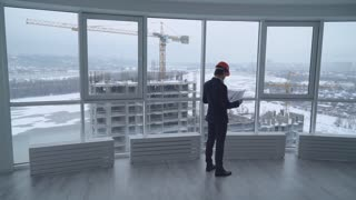 architect holding a design plan or other technical drawing looking on the project . worker in elegant suit and hard hat looking through the windows on the construction site with crane and workers on