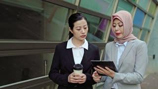 Asian and Muslim businesswomen walking and talking