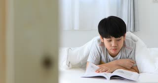 Asian cute boy rest on the bed and reading a book before final test at home .