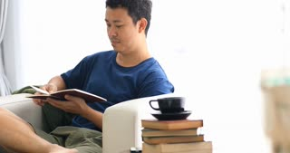 Asian man reading a book with smile face at home.