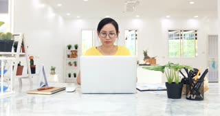 Asian Woman Working at home with Online Business. Asian woman is working with financial documents at home office with smile face.