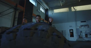 Athletic African-American man in black sportswear flipping large car tyre few times and recovering breath after exercise. Slow motion 4K shot on Red cinema camera.