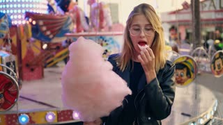 Attractive beautiful blonde skinny model woman stands in amusement park, in attractions and rides, glimmering lights and colors. She snacks and eats huge pink cotton candy with pleasure