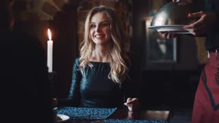 Attractive blonde woman in an elegant black dress sitting by the table with a man, lighten candle on the table, a waiter serves the gourmet dish. Restaurant interior on the background. Having a date.
