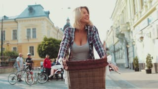 Attractive hot blonde woman with a short haircut, in casual wear riding vintage bike in the old city center and laughing happily. Happy moments, cheerful mood, positive emotions. Outdoor activities.