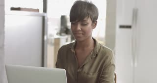 Attractive latina black woman wearing casual silk button up top typing on a laptop in a modern lof style office