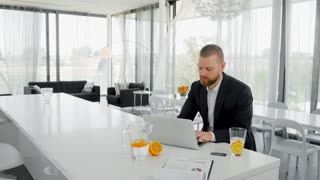 Attractive man sitting at table with notebook and holding credit card