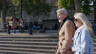 Attractive mature couple walking and talking in the city, in slow motion