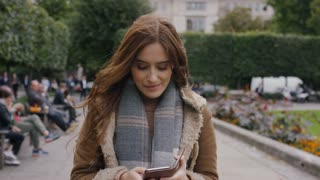 Attractive young female reading and using her phone as she walks, in slow motion