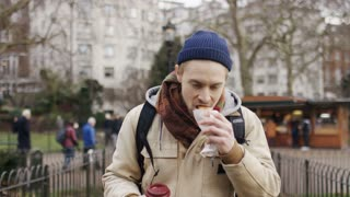Attractive young man walks in a park whilst eating and drinking, in slow motion