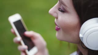 Attractive young woman with light makeup and red lips listens to music on the smart phone, and emotionally sings along. True emotions, pure feeling. Cheerful mood, being happy.