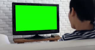 Back view of Asian child Play Computer Game Using with green screen on television.