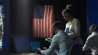 Back view of man and woman in space flight control center with digital tablet. Moon landing of spaceship module