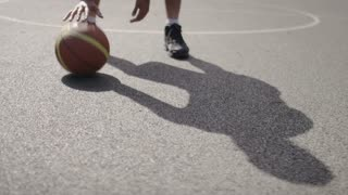 Basketball player dribbling the ball on an outdoor court, whilst looking to camera