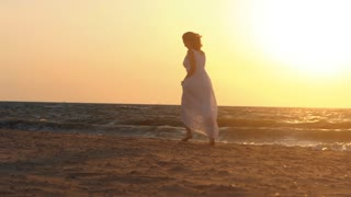 Beach woman running to water in dress at sunset raising arms enjoying freedom during summer holidays vacation travel. Beautiful happy Caucasian female girl outside. Slow motion