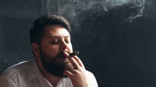 Bearded young man vaping with cigarette on background