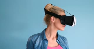 Beautiful Attractive Young Woman Using VR Glasses on blue background