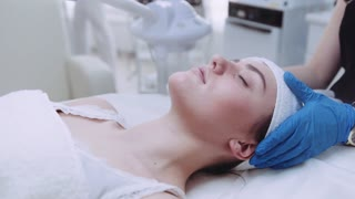 Beautiful brunette woman getting a professional facial treatment with steam in the beauty spa in slow motion. Natural beauty, modern beauty. Skin care, forever young. Hardware cosmetology.