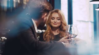 Beautiful couple of a young people sitting by the bar, having a glass of red wine and have flirting conversation. Handsome young man in a suit, and elegant blonde woman in luxurious black dress.
