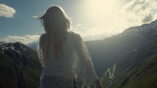 Beautiful girl on the top of the mountain, wind is playing with her hair, adorable nature around.