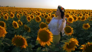 Beautiful girl with wreath running on yellow sunflower field, raising hands. Freedom concept. Happy woman outdoors. Harvest. Sunflowers field in sunset. Slow motion. Ukrainian style