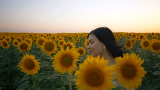Beautiful girl with wreath walking on yellow sunflower field. Freedom concept. Happy carefree woman outdoors. Harvest. Sunflowers field in sunset. Slow motion
