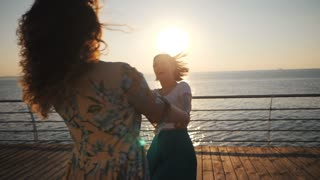 Beautiful girls whirling, dancing and playing on the embankment near sea or ocean. Friendship concept, slow motion