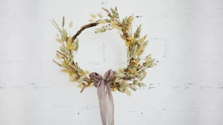 Beautiful hand made do it yourself wreath from dry flowers and grass and decorated with artisan designer silk ribbon, made for wedding or christmas decoration isolated in front of white brick wall