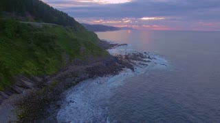 Beautiful mesmerizing picturesque epic drone footage from air of purple pink sunset, clouds and sun on horizon, high tide waves crush on shore of jungle forest mountains