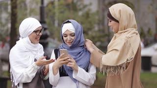 Beautiful Muslim Girl Using Smartphone and Laughing